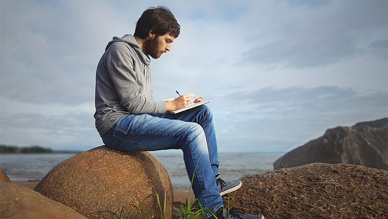 A man writes in a journal by the ocean