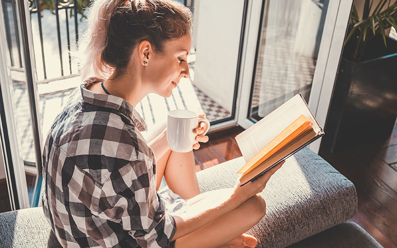 A student reads a book at home while enjoying a cup of coffee.