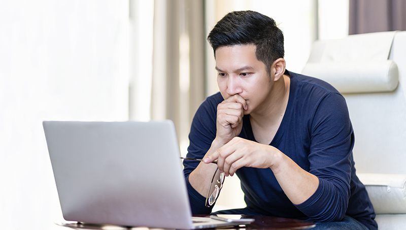 Young man watching videos on a laptop