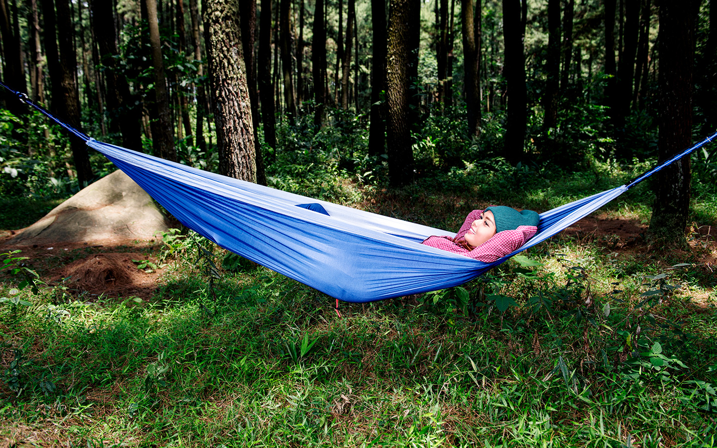 Woman relaxes in hammock in the woods