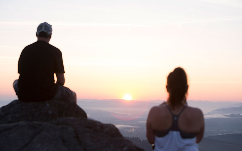 Two students watching the sunrise from the top of a mountain.