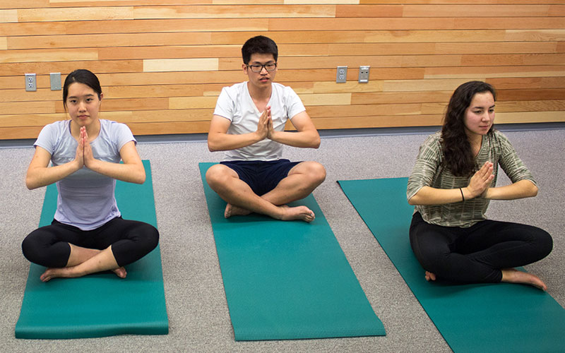 Three students doing yoga.